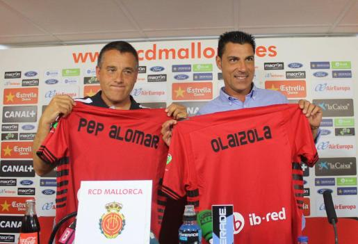 Pep Alomar y Javier Olaizola muestran camisetas del Real Mallorca en su presentación como nuevo cuerpo técnico del primer equipo.