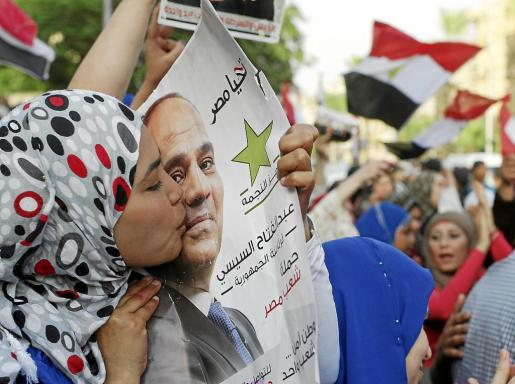 Una seguidora del general Al Sisi besa un póster con su imagen en el primer día de votación.