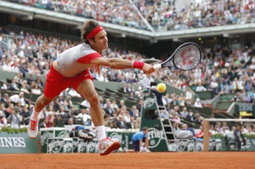 El tenista suizo Roger Federer devuelve la bola al ruso Dmitry Tursunov durante un partido de tercera ronda del torneo de tenis Roland Garros disputado este viernes 30 de mayo de 2014 en París.
