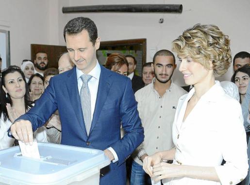 Bachar al Asad, acompañado por su esposa, deposita el voto en un colegio electoral de Damasco.
