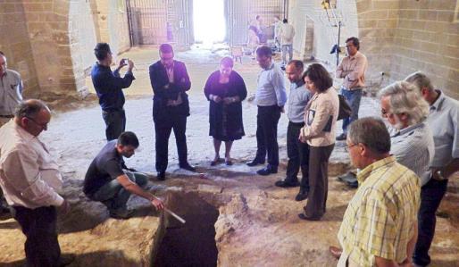 El arqueólogo Miquel Àngel Sastre muestra la tumba excavada en la iglesia de Santa Anna que linda con la zona visitable de la ciudad romana.