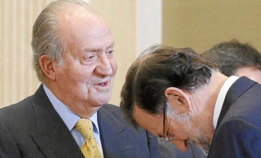 El rey saluda al presidente del Gobierno, Mariano Rajoy, durante la reunión anual de la Fundación Carolina.