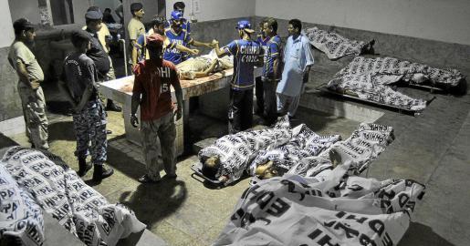 Equipos de rescate y soldados paramilitares contemplan los cuerpos en la morgue de un hospital de Karachi.