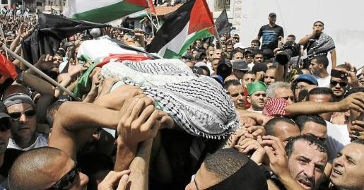 Escenas de dolor durante el entierro, ayer en su barrio de Jerusalén, del adolescente palestino asesinado esta semana.