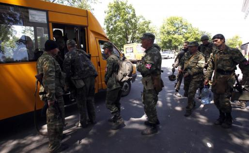 Armed pro-Russian separatists board a bus as they leave their positions in Kramatorsk in eastern Ukraine July 5, 2014. Pro-Russian rebels were pulling out of a flashpoint area of eastern Ukraine on Saturday as authorities in Kiev savoured a major military success in its three-month fight against the separatists. A Reuters reporter saw a convoy of around 20 military transport vehicles and buses filled with armed rebels driving out of Kramatorsk where they had gone after apparently earlier fleeing the separat