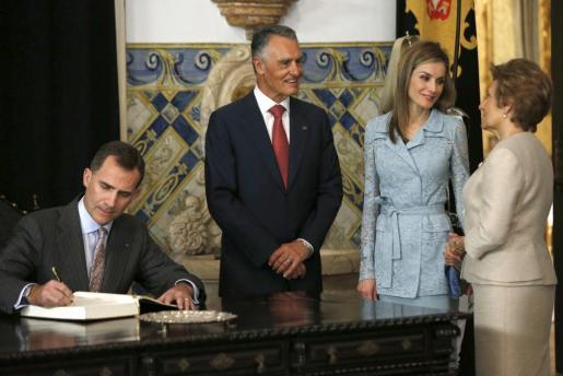 GRA180. LISBOA, 07/07/2014.- El Rey Felipe VI firma el libro de honor en presencia del presidente de la República, Anibal Cavaco Silva (2i), su esposa María Cavaco (d) y la Reina Letizia, durante la recepción ofrecida hoy en el Palacio de Belem, en Lisboa, con motivo del viaje de los Reyes de España a Portugal, el primero de su gira de presentación a los tres países vecinos. Esta gira tendrá su segunda etapa en Marruecos el próximo 14 de julio y continuará en Francia antes de que acabe el mes. EFE/Juan Carl