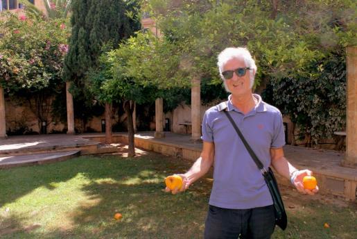 Miguel Gallardo sostiene dos naranjas del jardín del Centre de Cultura Sa Nostra (Palma).     CULTURA    PALMA