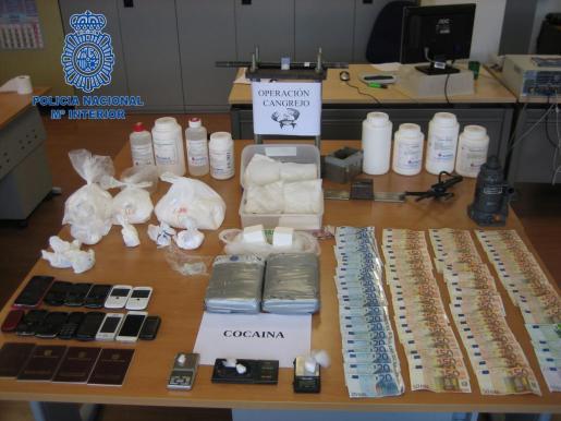 Material de los traficantes incautado por la policía nacional que incluye cocaína y dinero en efectivo.
