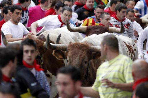 Varios mozos corren delante de los toros de la ganadería gaditana Fuente Ymbro en la curva de Telefónica, durante el sexto encierro de los sanfermines 2014.