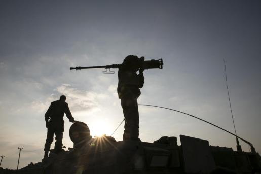 Un saldado israelí porta un arma pesada durante el ataque de este lunes sobre Gaza.