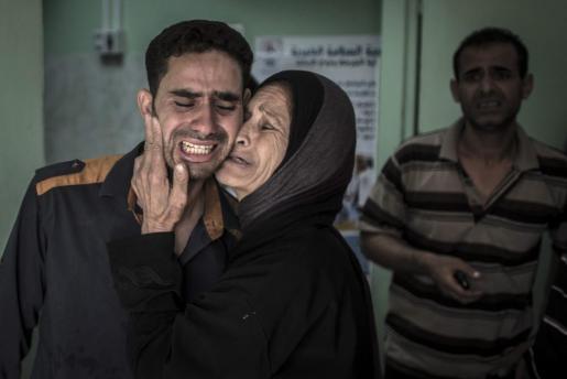 Dos palestinos lloran la muerte de un familiar en el bombardeo a una escuela de la ONU que ha dejado 20 víctimas mortales y medio centenar de heridos.