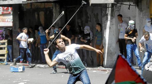 Dos palestinos arrojan piedras con hondas contra soldados israelíes durante una manifestación en la ciudad cisjordana de Hebrón.
