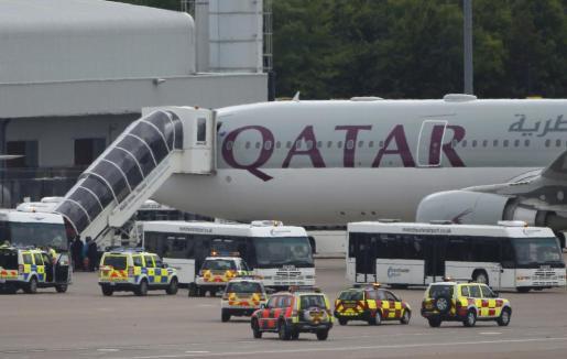 Las fuerzas de seguridad inglesas desembarcan el equipaje del avión de Qatar Airways sobre el que pesaba una amenaza de bomba que finalmente resultó ser falsa.