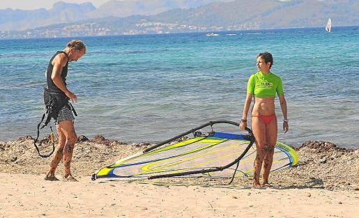 Cerca de la orilla, ella espera a que él se ponga a punto para hacer 'surfing' durante un rato.