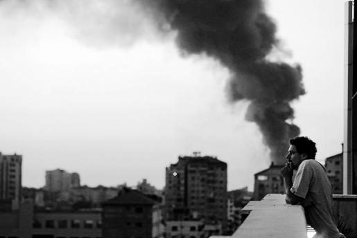 Associated Press video journalist Simone Camilli stands on a balcony with smoke from Israeli strikes billowing in the background, in Gaza City in this August 2014 photo. Italian journalist Camilli, three Palestinian bomb disposal experts and two other people were killed in Gaza on Wednesday when unexploded munitions blew up, medical officials and police said. REUTERS/Lefteris Pitarakis/AP Photo/Handout via Reuters (GAZA - Tags: POLITICS CIVIL UNREST CONFLICT MEDIA PROFILE)  ATTENTION EDITORS - THIS IMAGE