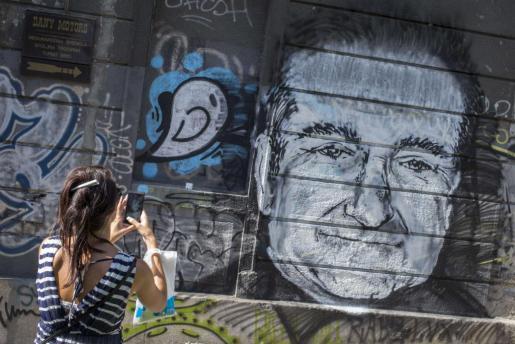 Una mujer fotografía un mural con el rostro del actor Robin Williams en Belgrado.