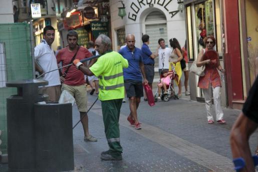 Un trabajador de Emaya se encarga de unas papeleras.