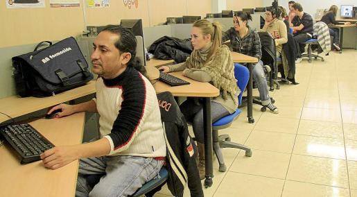 Trabajadores, realizando un curso de formación para perfeccionar sus conocimientos de informática.