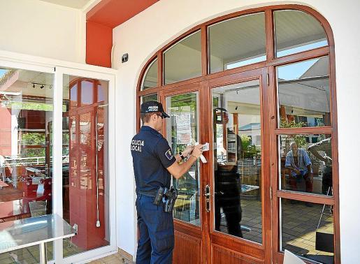Un agente de la Policía Local precinta el establecimiento denunciado. g Foto: MICHELS