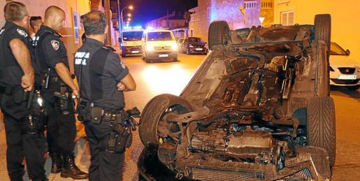 Agentes de la Policía Local, ante el vehículo que volcó en el Vivero, en Palma.