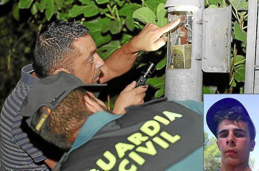 Un técnico y un agente de la Guardia Civil examinan la farola donde se electrocutó el joven (imagen de la derecha).