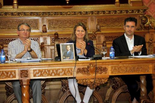 María Salom, entre Joan Rotger y Jaume Juan, aplaude tras aprobarse el nombramiento de Rafael Nadal como Hijo Predilecto de Mallorca.