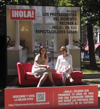 """Dos mujeres posan en un decorado creado por la Revista ¡Hola! para celebrar sus 70 años de vida, con """"Grandes Momentos"""", una exposición con 70 de sus portadas más emblemáticas en el Paseo de Recoletos hasta la Plaza de Neptuno de Madrid."""
