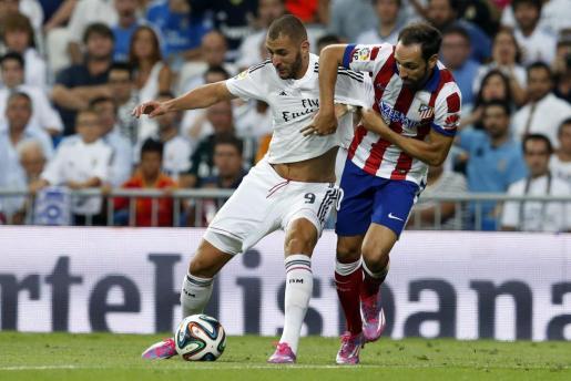 El delantero francés del Real Madrid Karim Benzema (i) protege el balón ante el defensa del Atlético de Madrid Juanfran Torres, durante el partido de ida de la Supercopa de España.