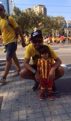 El central del FC Barcelona y la selección española Gerard Piqué junto a un nilño durante la manifestación de la Diada.