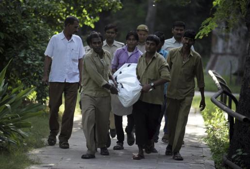 Varios hombres trasladan el cuerpo de un joven fallecido tras ser atacado por un tigre blanco en el zoo de Nueva Delhi (India) este martes 23 de septiembre de 2014.