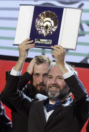 El realizador Carlos Vermut (detrás) y el productor Pedro Hernández reciben la Concha de Oro por su película 'Magical Girl'.