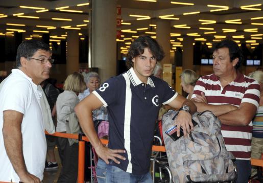 Rafael Nadal, en el aeropuerto con su tío Toni, también entrenador (izquierda), y su padre.