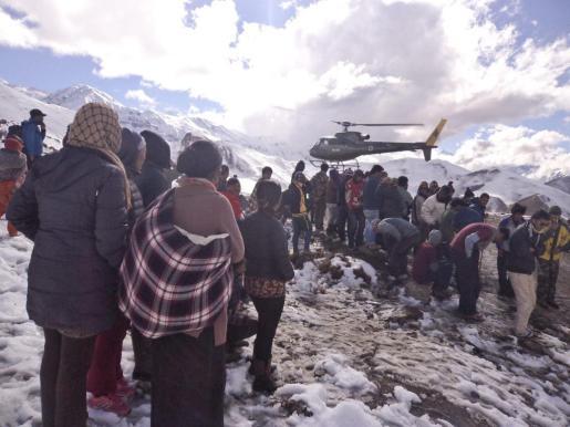 """Fotografía facilitada por el ejército nepalí de varias personas que observan el aterrizaje de un helicóptero de rescate en Mustang, Nepal, este miércoles 15 de octubre de 2014. Al menos diecisiete montañeros -entre ellos cuatro canadienses, dos polacos, un israelí, un indio y un nepalí- han muerto mientras hacían """"trekking"""" en el Himalaya."""