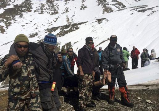 Fotografía facilitda por el ejército nepalí, de soldados que trasladan a dos montañeros heridas en el paso Throung La del circuito de Annapurna, Mustang, Nepal, este viernes 17 de octubre de 2014. Nepal sufre una de sus peores tragedias turísticas y de montañismo con la muerte de 27 personas.