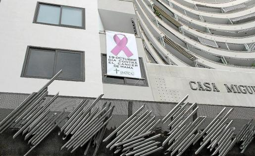 Un gran lazo rosa preside uno de los balcones del edificio del Passeig Mallorca.