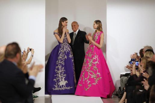 Imagen de archivo del diseñador junto a dos modelos durante un desfile.