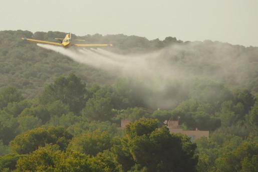 Una avioneta fumigando cerca de unas viviendas.