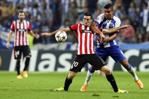 El centrocampista brasileño del Oporto, Carlos Henrique Casemiro lucha por el balón con el delantero Ardid Aduriz del Athletic de Bilbao durante el partido de la Liga de Campeones disputado en el estadio Dragao de Oporto.
