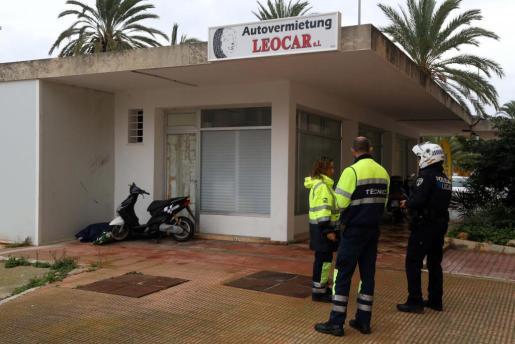 Dos técnicos de ambulancia junto a un Policía Local y, al fondo, tras la moto, el cadáver.