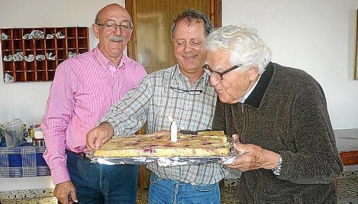 El padre Barceló sopla la vela conmemorativa en un pastel que sostiene el prior de Sant Honorat, Miquel Mascaró, en presencia de Antoni Cerdà.