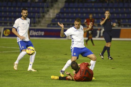 El jugador del Mallorca, Arana, cae al suelo ante la mirada de dos futbolistas del Tenerife.