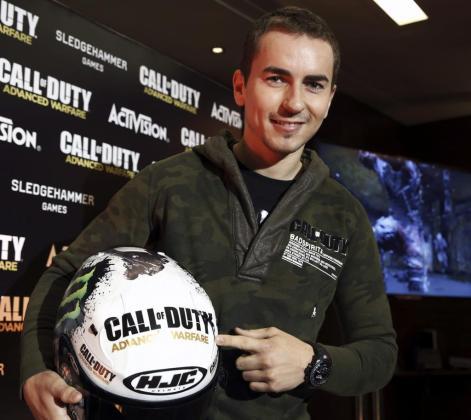 El piloto español Jorge Lorenzo (Yamaha YZR M 1), posa junto a su casco decorado con la imagen del nuevo videojuego 'Call of Duty: Advanced Warfare'.