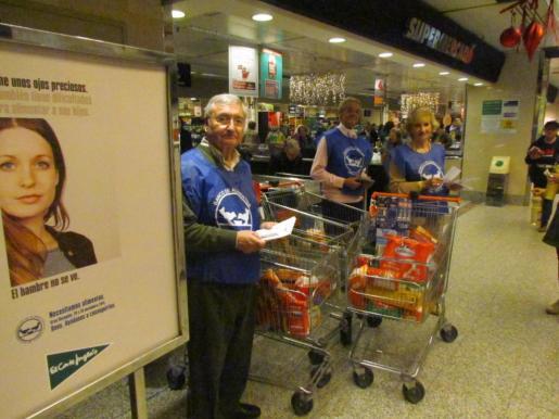 Miembros del Banco de Alimentos con carros de la compra llenos de alimentos.