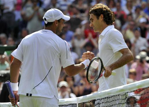 Roger Federer saluda a Alejandro Falla tras el encuentro.