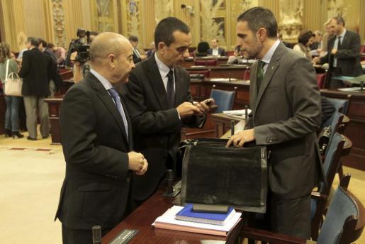 Los consellers de Presidència, Antoni Gómez; de Economia, Joaquín García y el de Hisenda, José Vicente Marí, charlan en el Parlament.