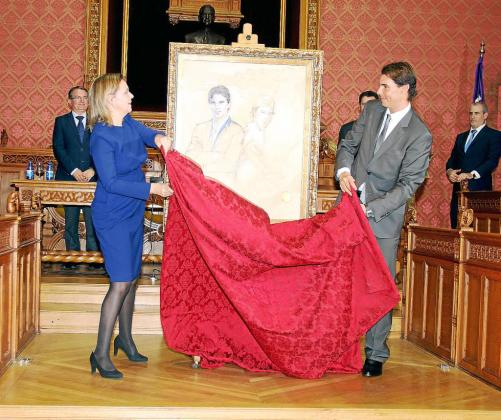 Momento en el que la presidenta del Consell de Mallorca, Maria Salom, y Rafa Nadal descubren el retrato del tenista, obra de Ángeles Cereceda, que se unirá a partir de ahora al resto de retratos de 'fills predilectes' en el salón de plenos de la institución.