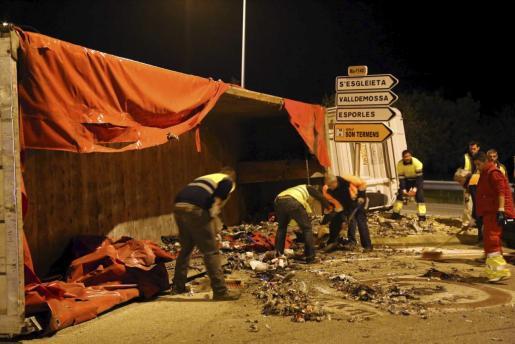 Los operarios retiran de la calzada los restos de la basura que se desparramó tras volcar un camión en la carretera de Sóller.