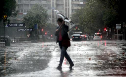 Una mujer camina bajo la lluvia.