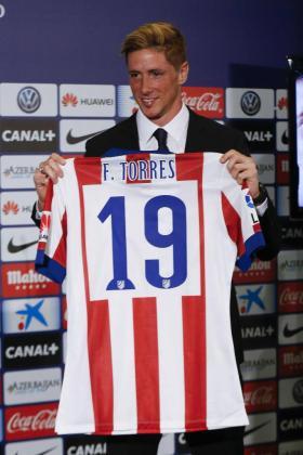 El delantero Fernando Torres muestra la camiseta que lucirá con el Atlético de Madrid.