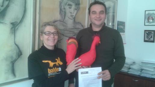 La representante de Baldea, Nieves Martín, entregando el gallo al alcalde de Pollença, Bartomeu Cifre.